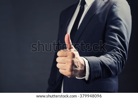 Businessman in suit showing Good sign with his thumb up on black background - stock photo