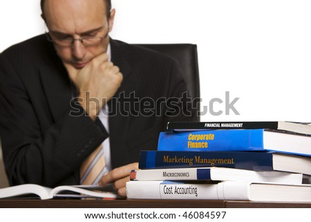 Businessman in suit sitting at desk in office in front of a stack of business books studying information, white background - stock photo