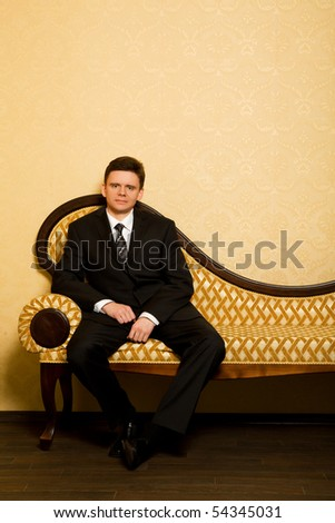 businessman in suit sitting on sofa in room - stock photo