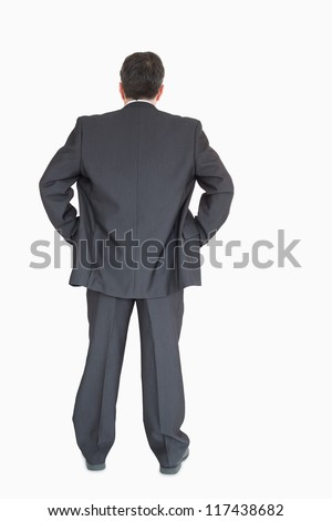 Businessman in suit standing back to the camera with hands on hip