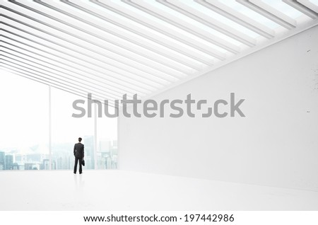 businessman in suit standing in big white office - stock photo