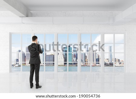 businessman in suit standing in room and looking at window