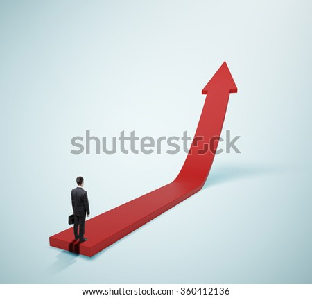 businessman in suit standing on red arrow - stock photo