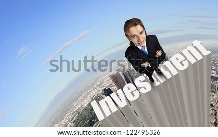 Businessman in suit standing on the word Investment