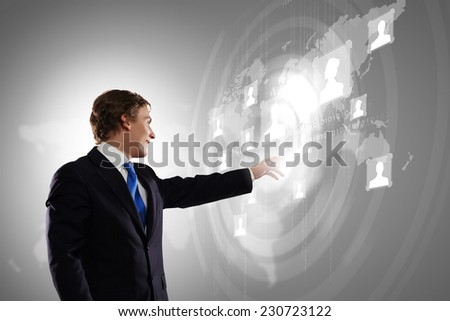Businessman in suit touching icon of media screen