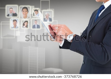 Businessman in suit using digital tablet against grey vignette