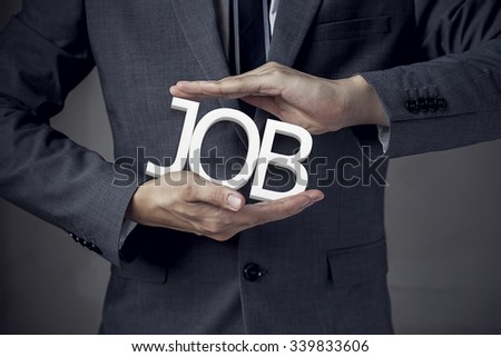 """Businessman in suit with two hands in position to protect the word """"JOB"""" (focus on hand, blur out the suit). - stock photo"""