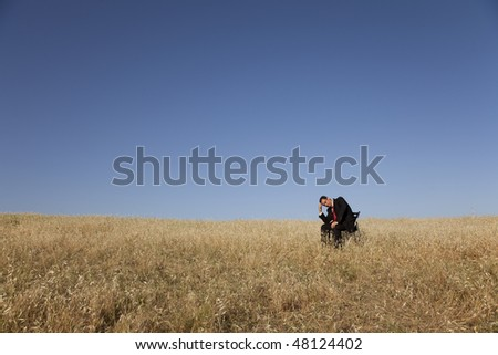 businessman in the field sited in a chair - stock photo