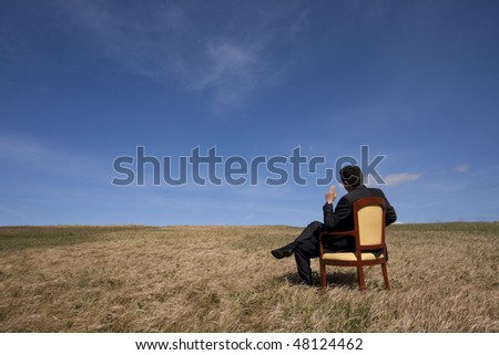 businessman in the field sited in a chair