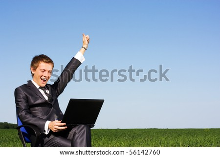 Businessman in the field, with a laptop. Happy, successful - stock photo