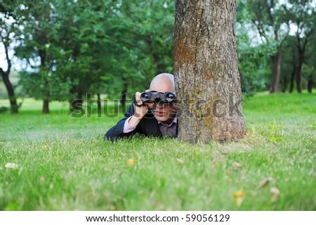 Businessman in the green park looking through binoculars - stock photo