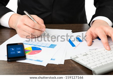 businessman in the office of the table with graphics and phone - stock photo