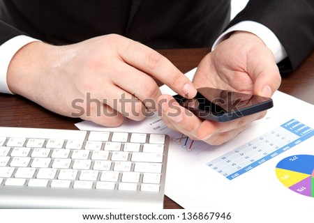 businessman in the office of the table with graphics holding a phone - stock photo