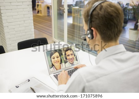 Businessman in the office on video conference, headset, Skype - stock photo