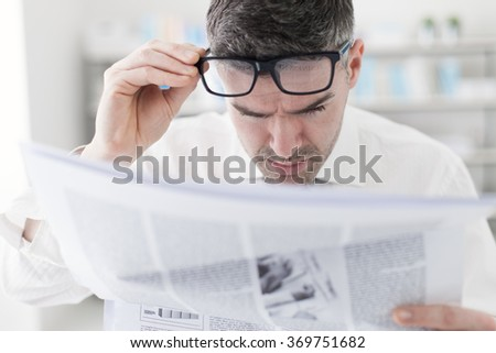 Businessman in the office, reading bad breaking news on a financial newspaper, he is shocked and adjusting his glasses