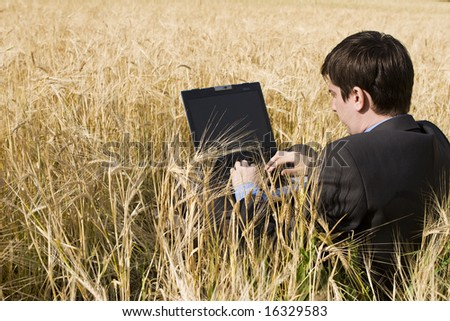 businessman in wheat field with notebook