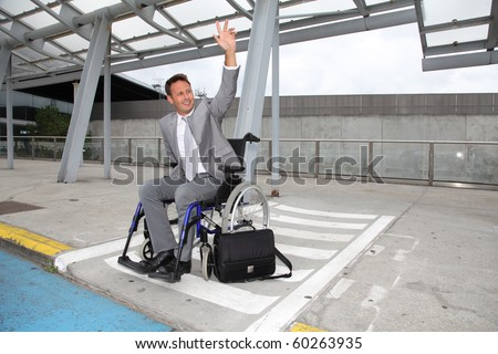 Businessman in wheelchair waiting for a taxi - stock photo