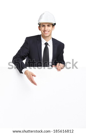 Businessman in white hard hat pointing hand gestures at copyspace, isolated on white. Concept of success and advertisement - stock photo