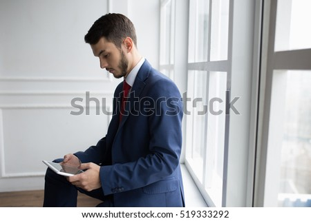 Businessman in white office using digital tablet sitting on windowsill