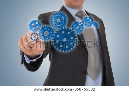 businessman indicate a cog gear - stock photo