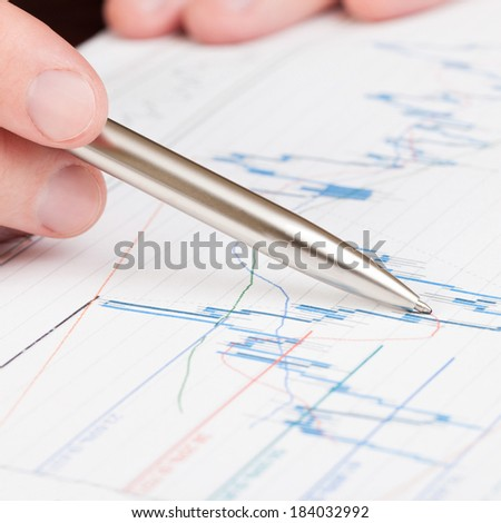 Businessman indicating on diagram of financial report with pen - 1 to 1 ratio - stock photo
