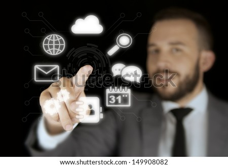 Businessman Interacting with a Virtual Interface on a Black Background - stock photo