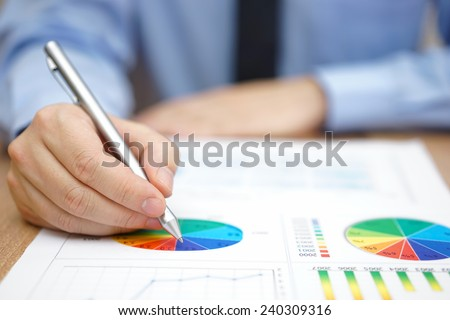 Businessman is analyzing business report with charts and diagrams - stock photo