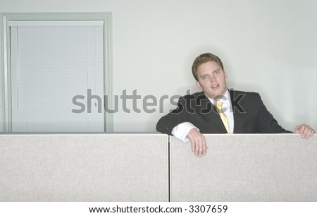 Businessman is bored and sits above his cubicle in his office looking at the camera with his business suit on