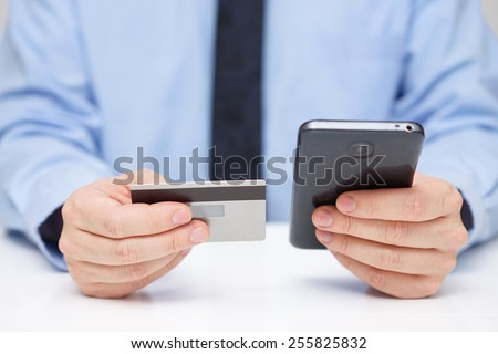 Businessman is buying application  with  credit card on mobile phone - stock photo