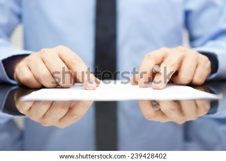 businessman is carefully reading contract - stock photo