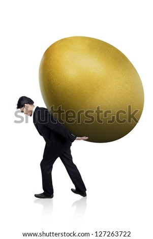 Businessman is carrying a huge golden egg isolated on white