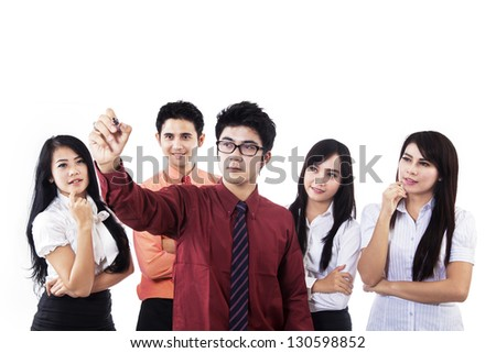 Businessman is drawing something while his team looking at copy space - stock photo