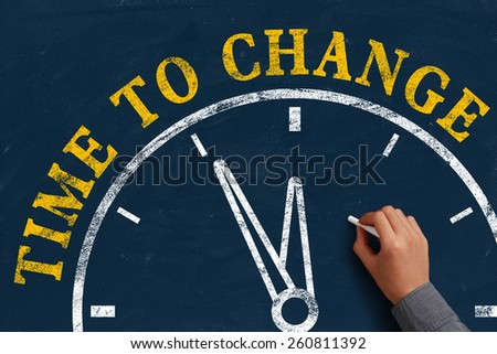Businessman is drawing the concept of time to change on chalkboard. - stock photo