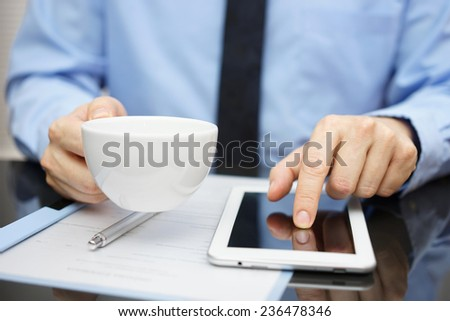 businessman is drinking coffee and working on tablet computer - stock photo