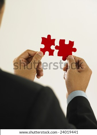 businessman is fixing the red color puzzle