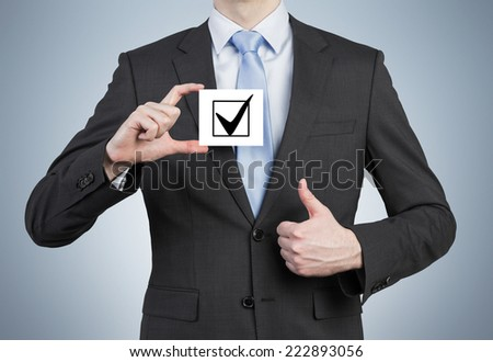Businessman is holding a checkbox, a concept of decision making process. - stock photo