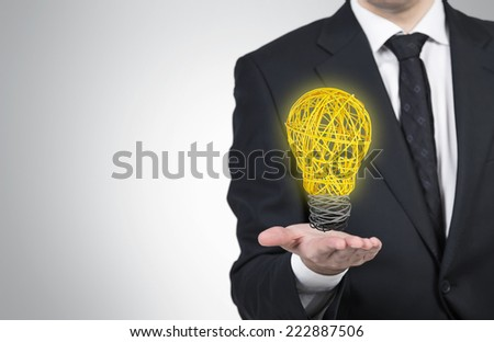 Businessman is holding a lightbulb made of wires. - stock photo