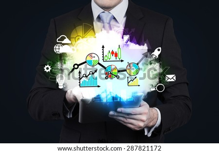 Businessman is holding a tablet with flying out graphs and chars.