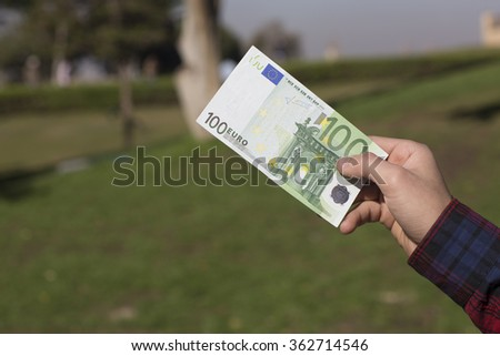 Businessman is holding Euro banknotes in outdoor  - stock photo