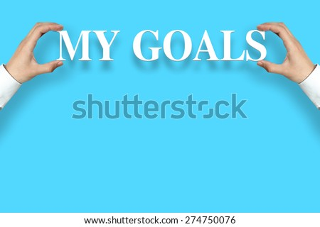 Businessman is holding the My Goals text against the blue background with copy space. - stock photo