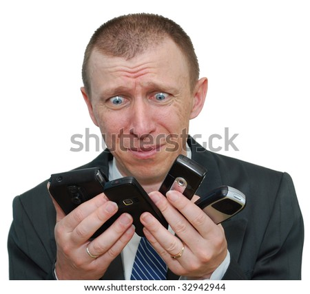 Businessman is in panic. All his cell phones are ringing. He can't choose the right one. - stock photo