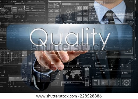 businessman is pressing a button with the inscription: Quality , in background are some graphs and diagrams - stock photo