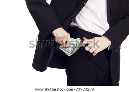 Businessman is putting money in his pocket. Isolated over white