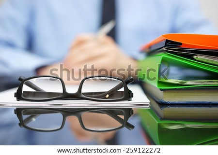 Businessman is reading or thinking in front of contract and documentation with glasses in focus - stock photo