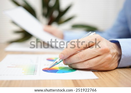 Businessman is reading report and checking data on graph - stock photo