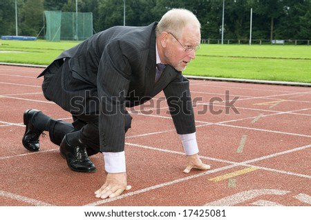 Businessman is ready for the start of his run. - stock photo