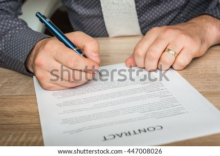 Businessman is signing a contract - business concept