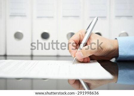 businessman is signing contract with binders in background - stock photo