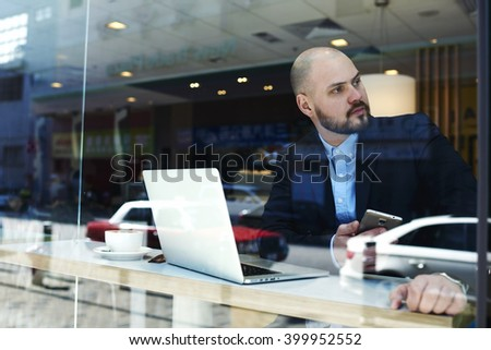 Businessman is sitting in cafe with laptop computer and waiting lawyer for approval of official documents. Confident male restaurant owner with mobile phone in hand is monitoring the work of his staff - stock photo