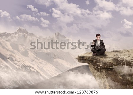 Businessman is sitting with his laptop on top of a mountain